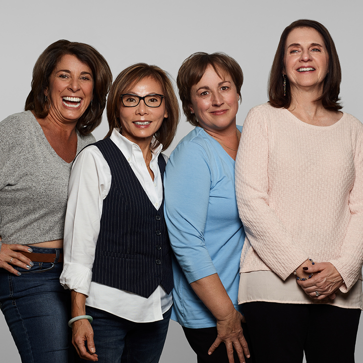 Color photo of (4) women standing posing for camera with natural smiles.