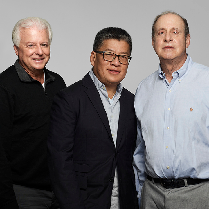 Color photo of 3 men portrait standing waist up, smiling naturally for the camera.