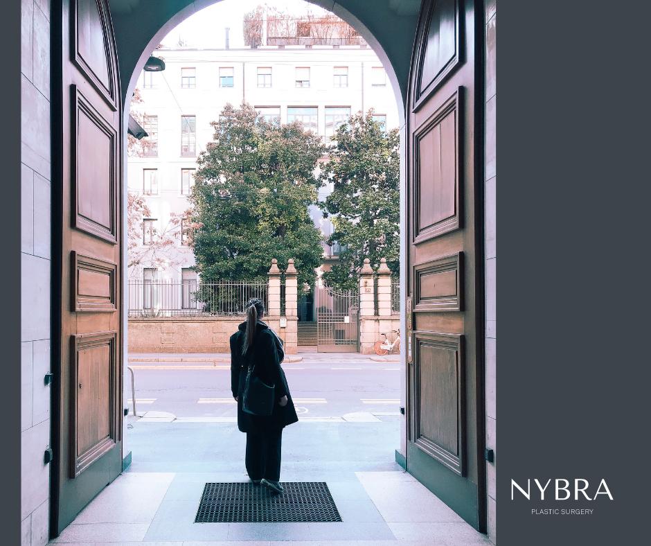 Woman walking outside two very large doors. Doors open to empty street.