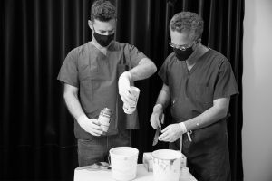 Black and white photo of Dr. Israeli and Dr. Bank focused on preparing the materials that will be painted on models for life cast,