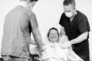 Black and white photo of model smiling happily with eyes closed as Drs. Israeli and Bank on either side prepare the life cast.