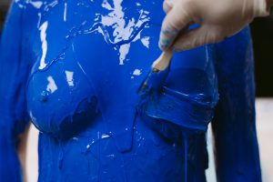 Close up of blue molding being painted on chest area with a paintbrush.