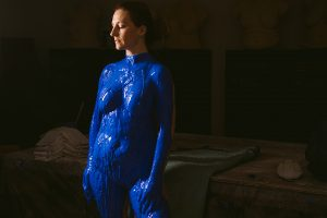 Model looking at ground as she stands with blue life casting.