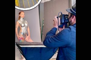 Model posing with silver body paint with photographer in foreground snapping a shot.