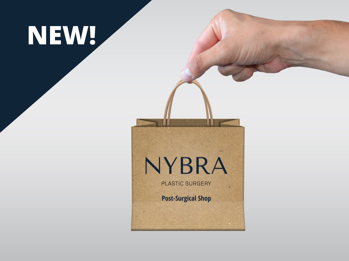 Photo of woman holding tiniest brown shopping bag with NYBRA Plastic Surgery Post-Surgical Shop on it.