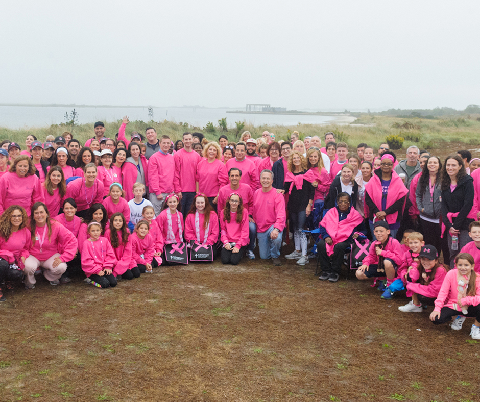 NYBRA Plastic Surgery team in pink sweatshirts pose together for the camera in group shot.